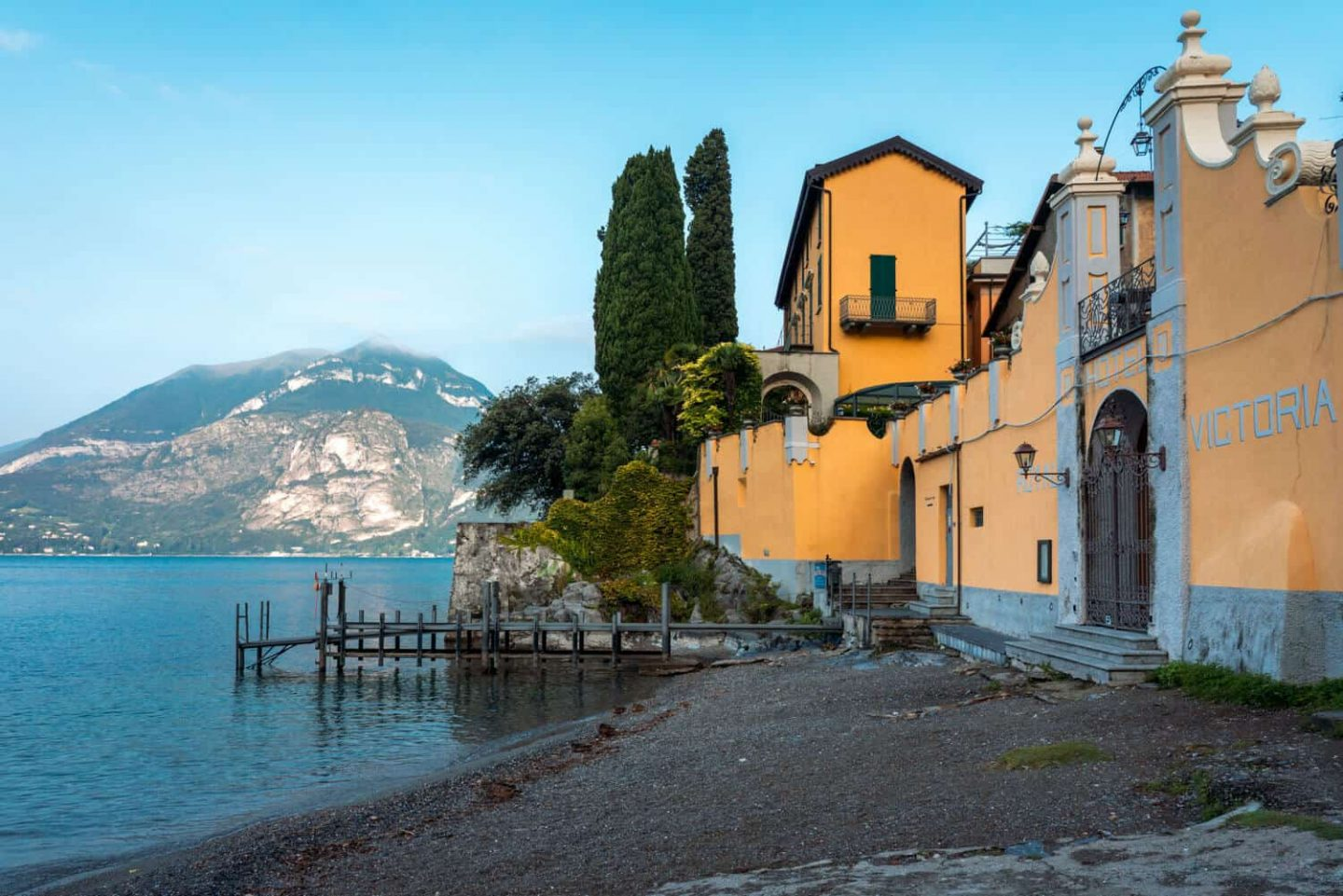 A pebble beach with a yellow building and mountain backdrop in Varenna  during a day trip from Milan to Lake Como