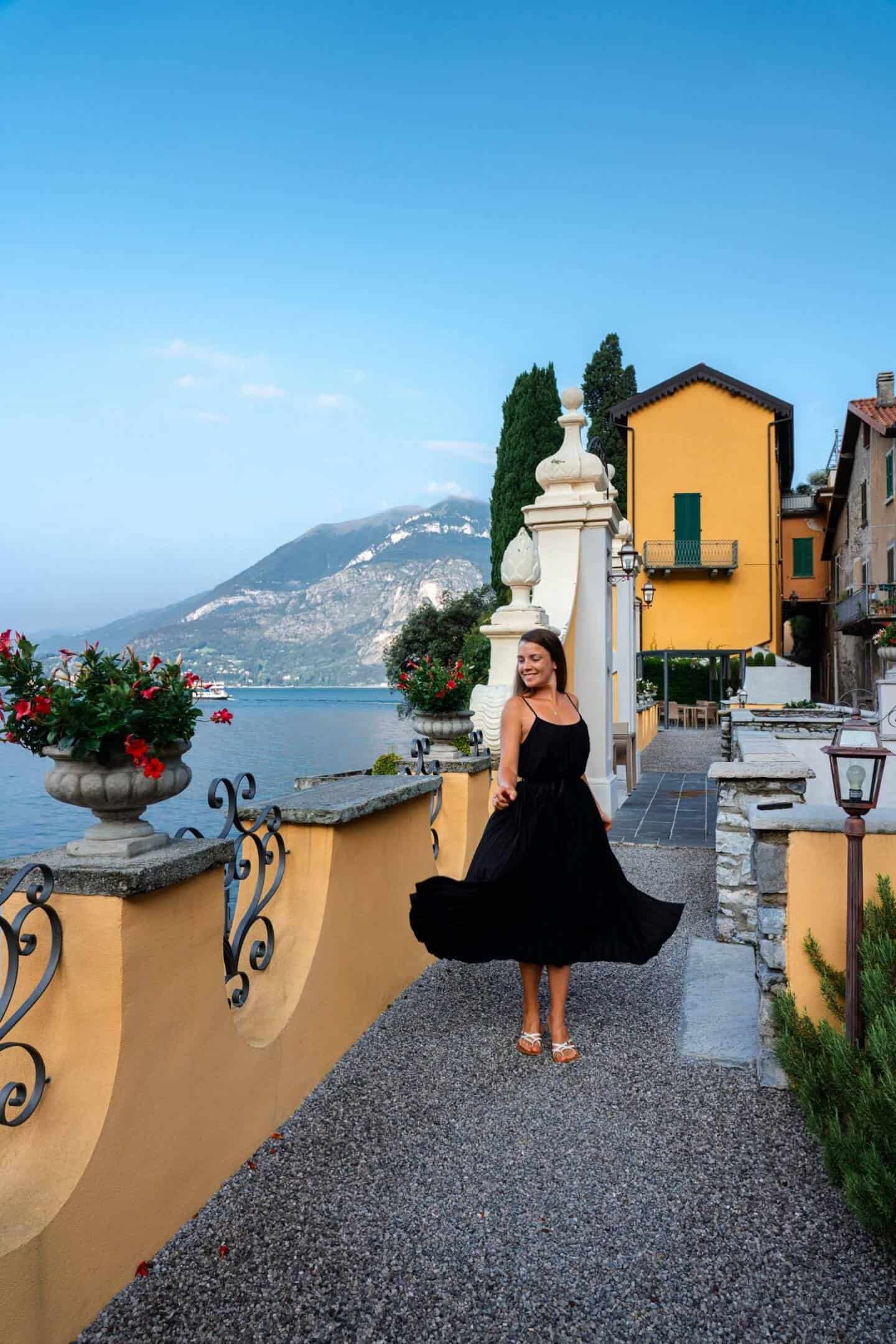 Girl twirling in  surrounded by a yellow building front of Lake Como on a Day trip from Milan