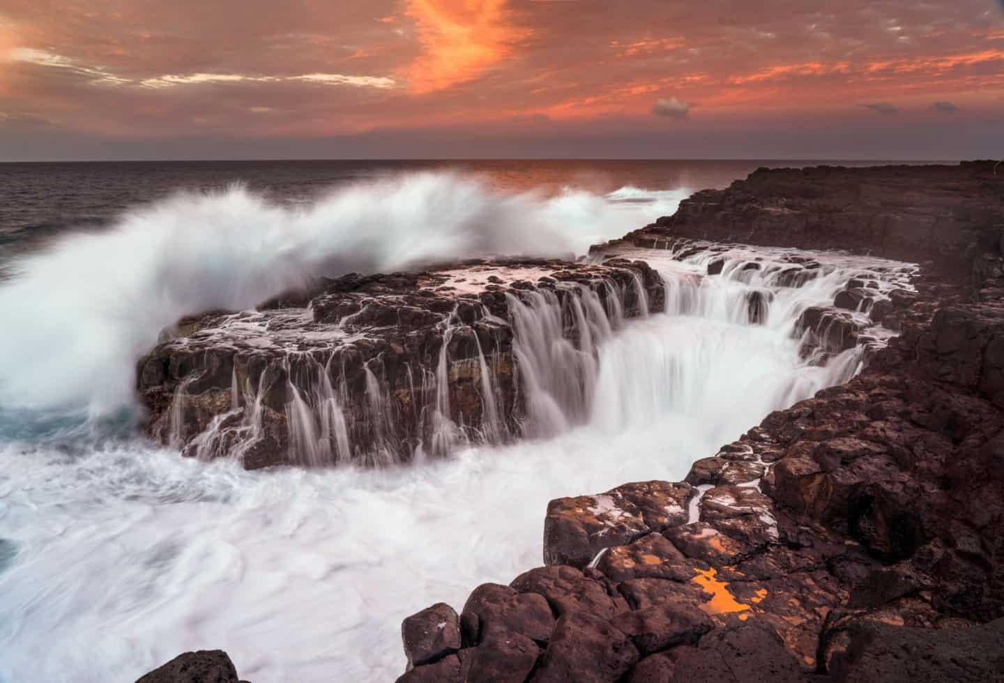 Amazing Kauai sunset photography at Queen's Bath on the north shore.