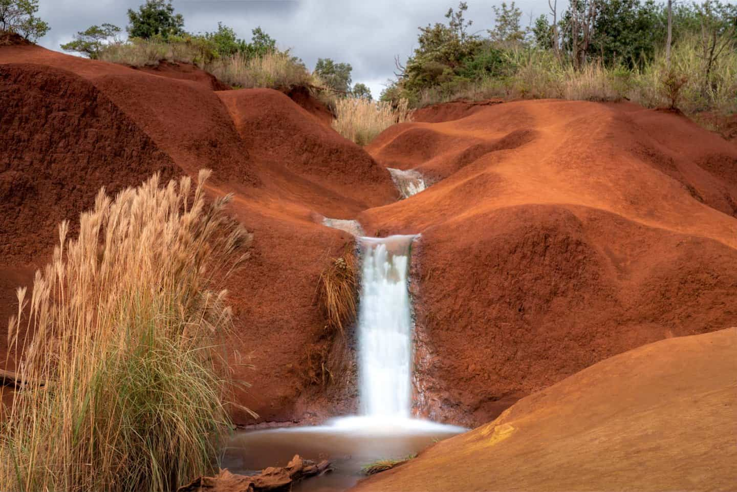 Long exposure Kauai landscape photography of a small waterfall flowing through the famous red dirt of Kauai.