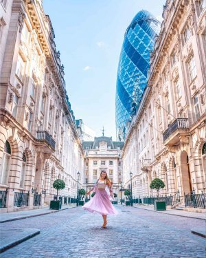 Girl twirling in St Helens Place with the Gherkin building visible behind