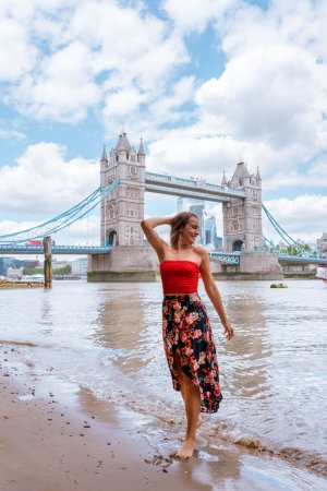 A girl exploring the banks of the River Thames at low tide with Tower Bridge behind.
