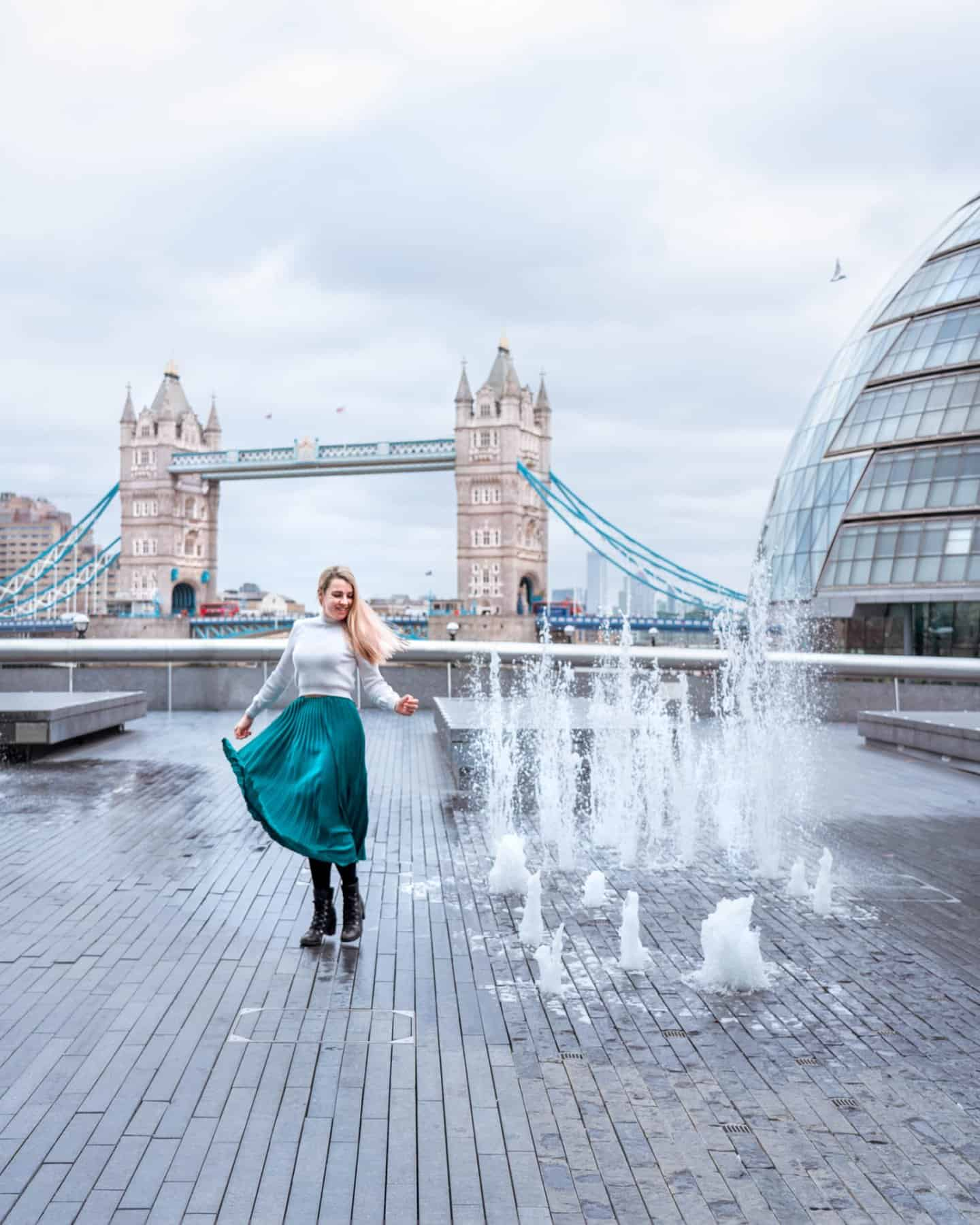A girl twirling next to the water fountains by City Hall with Tower Bridge in the background
