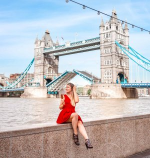 A girl in a red dress in front of Tower Bridge opening in London