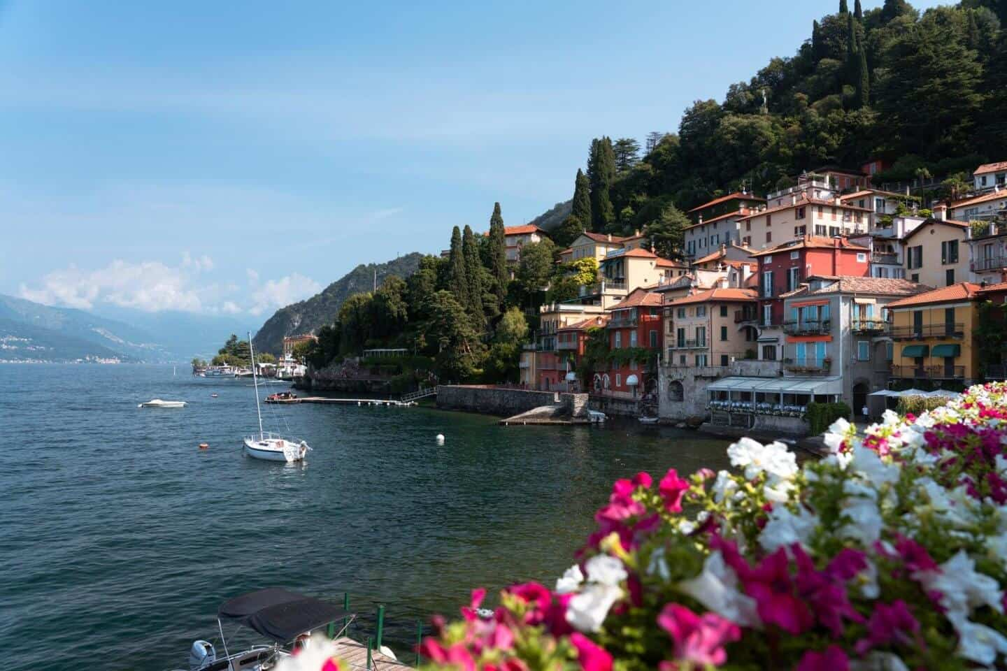 Flowers and colourful houses looking back towards the pier and Passeggiata degli Innamorati (lovers walk) from Riva Grande, Varenna, Lake Como