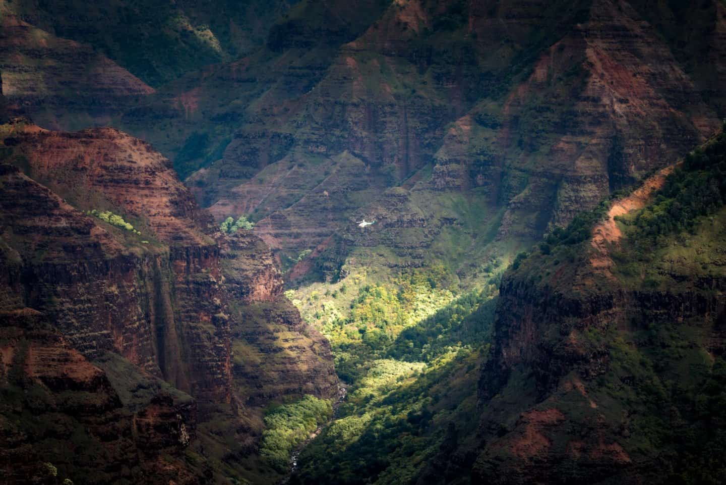 A helicopter photography tour descends deep into the Waimea Canyon.