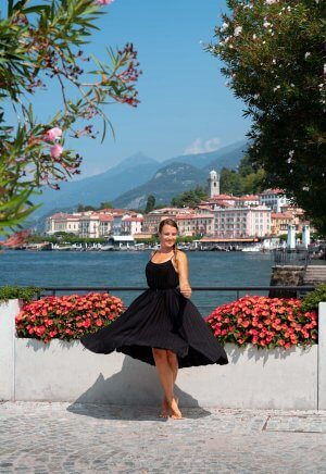 A girl twirls in front of pretty red flowers that decorate the lakeside promenade with stunning views back towards Bellagio town centre.