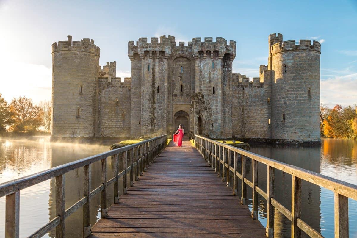 A girl in a red dress in front of Bodiam Castle at sunrise with mist rising from the moat creates a fairytale like feel at one of the best castles near London.