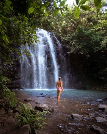 A girl standing in front of Ellinjaa Falls waterfall near Cairns