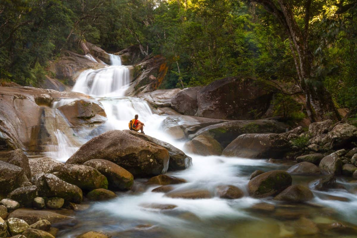 A hiker sits and rests by Josephine Falls near Cairns.