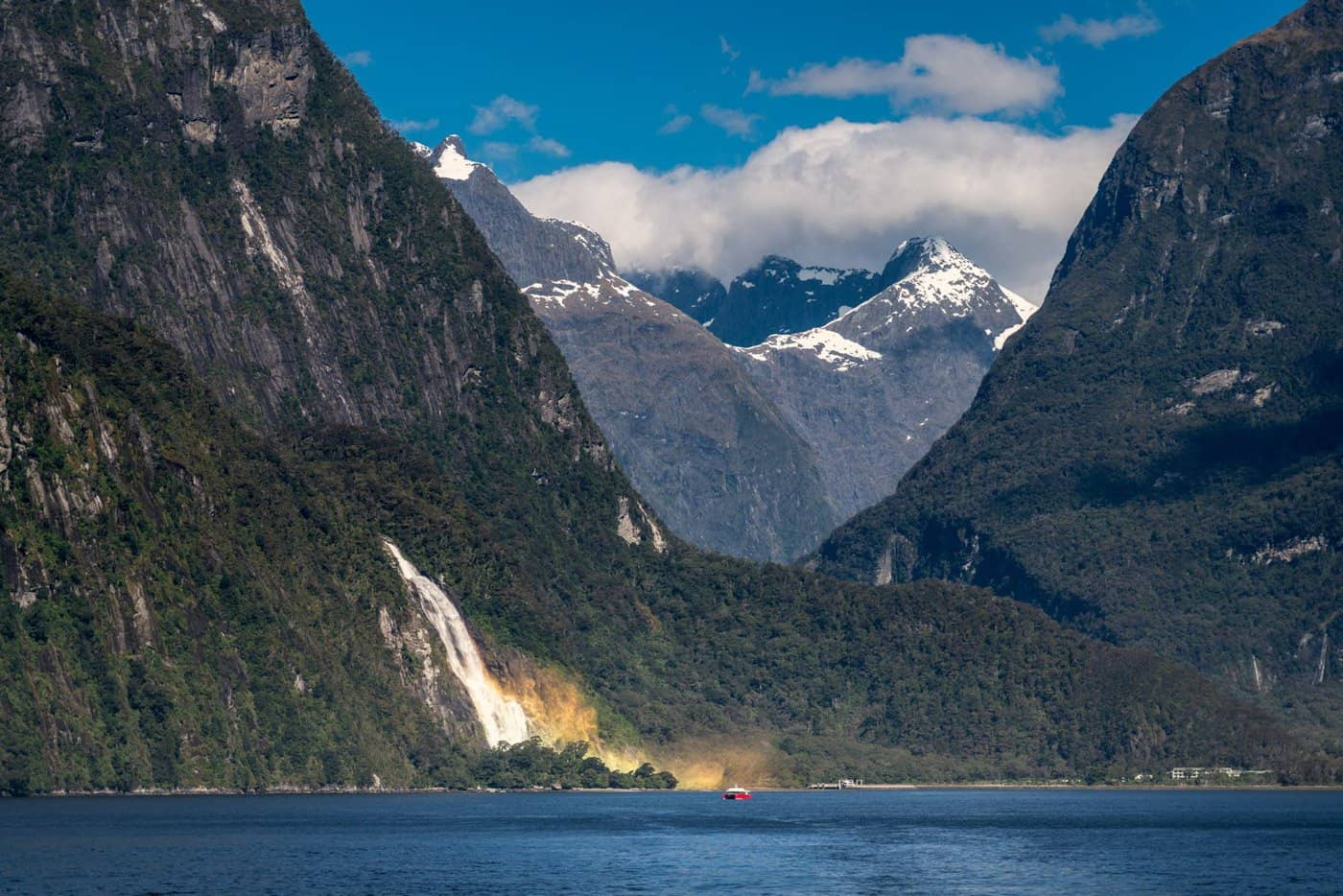 A waterfall and rainbow in Milford Sound, Fiordland National Park, New Zealand - a dream destination to visit.