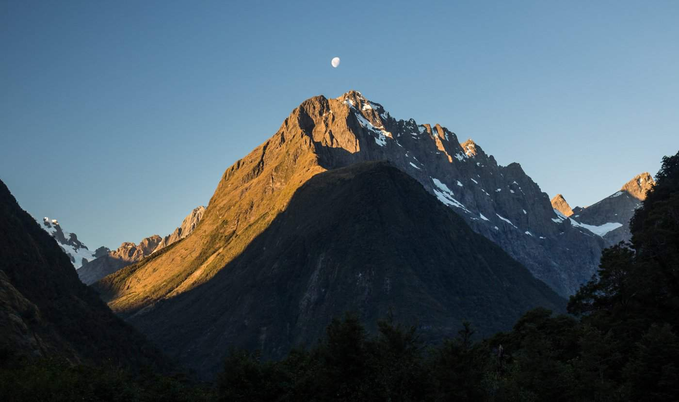 A view of a moon over distant peaks from The Chasm parking lot near Milford Sound.