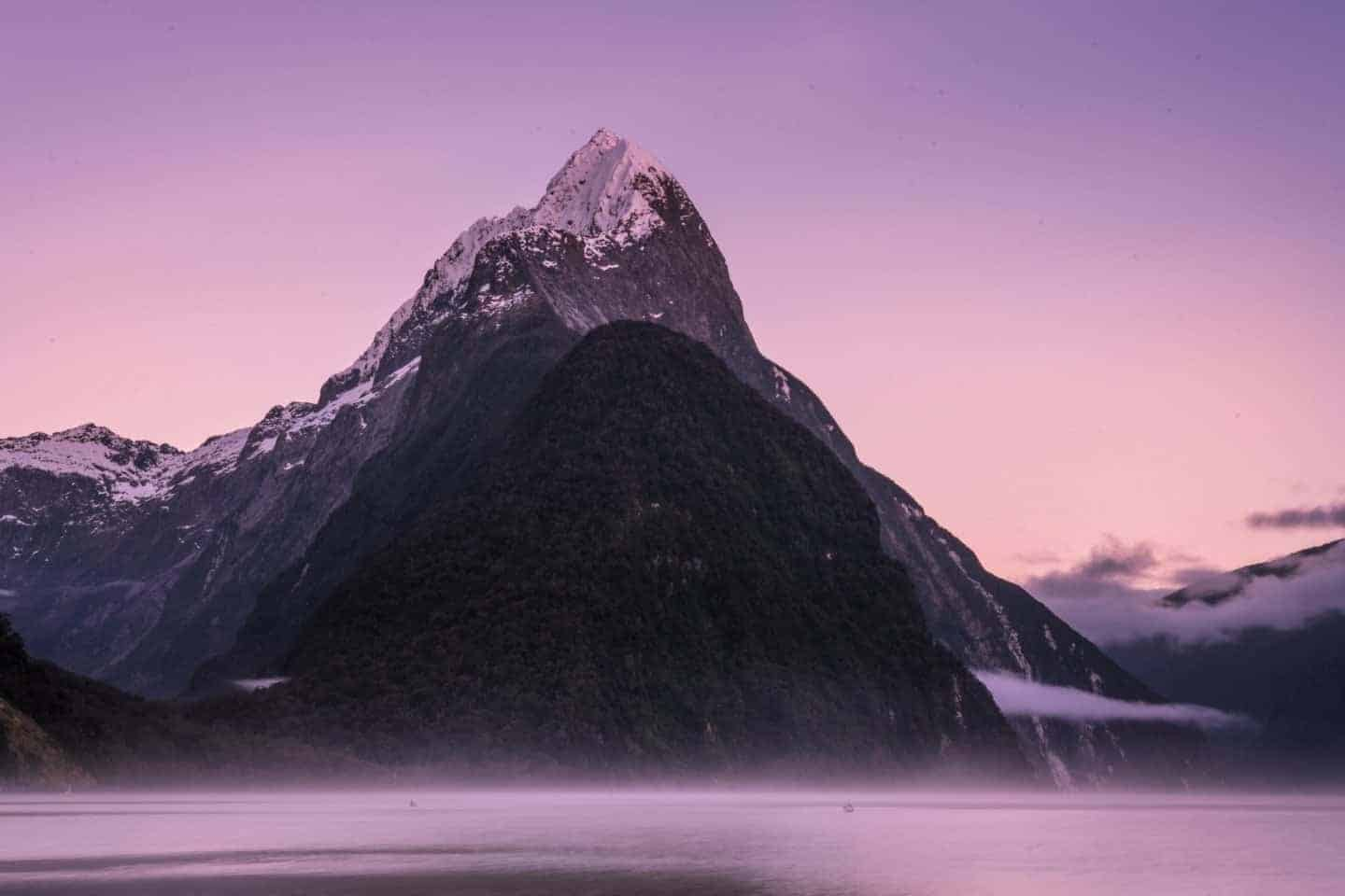 A snow-capped Mitre Peak looms tall on a moody morning at Milford Sound in this NZ landscape photograph.