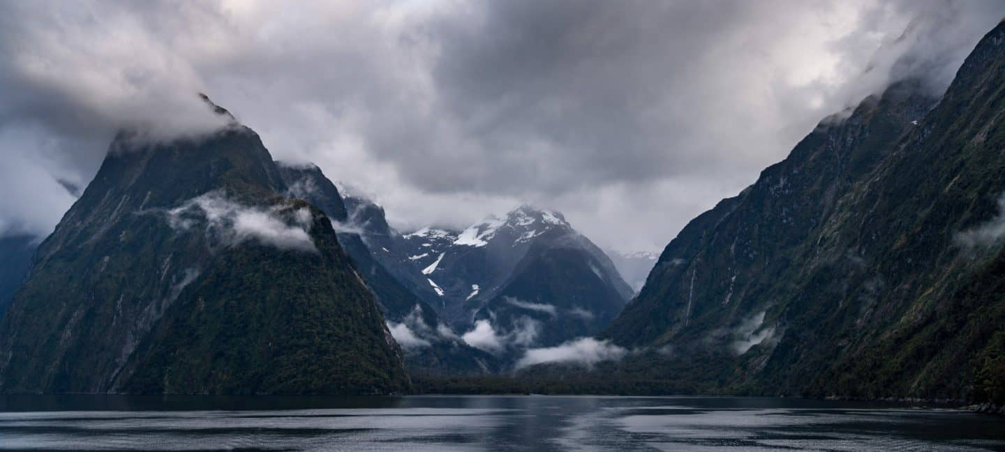 Low clouds create a dramatic landscape photograph at Milford Sound in New Zealand.