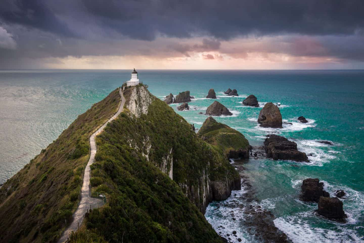 An early morning storm blows through, providing dramatic skies for this photograph of Nugget Point Lighthouse in the Catlins Forest Reserve.