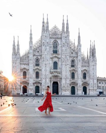A girl twirling in a red dress in front of Milan Cathedral at sunrise as the sun creates a starburst effect.  A beautiful way to start 2 days in Milan itinerary.