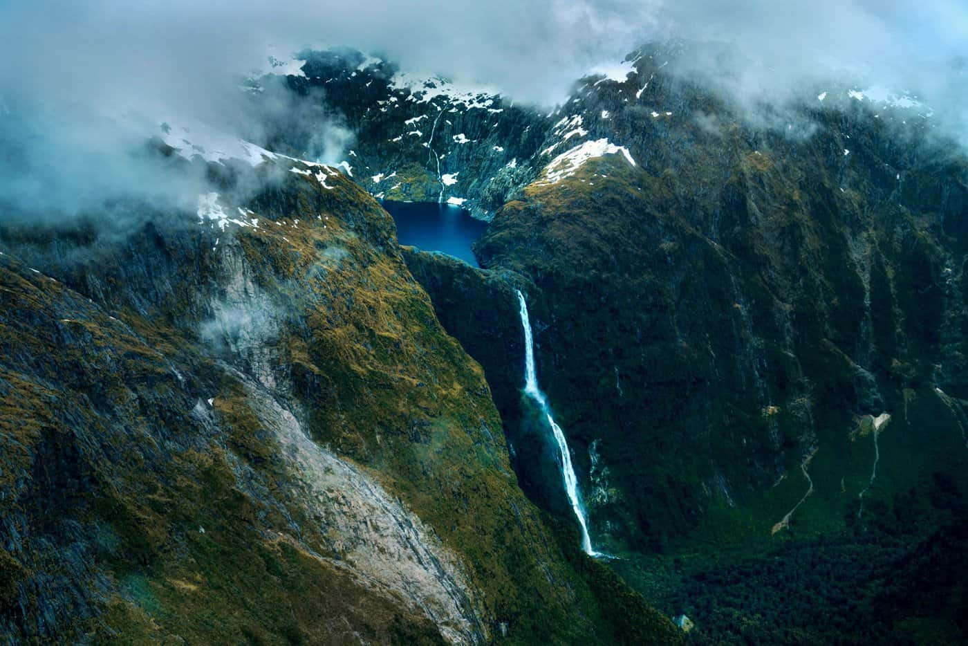 A mountain lake feeds into a waterfall on a scenic flight from Queenstown to Milford Sound.