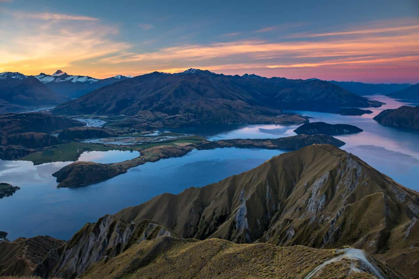 Roys Peak sunset photography is beautiful but challenging as the scenery will be in shadow long before the sky gets its color.