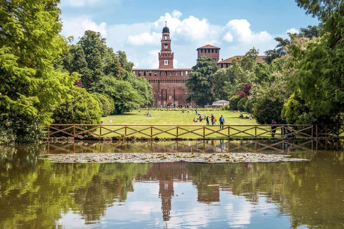 View of Sforza Castle from Sempione Park, Milan, Italy.  The castle is reflected in the water of the lake and people are resting on the grass.