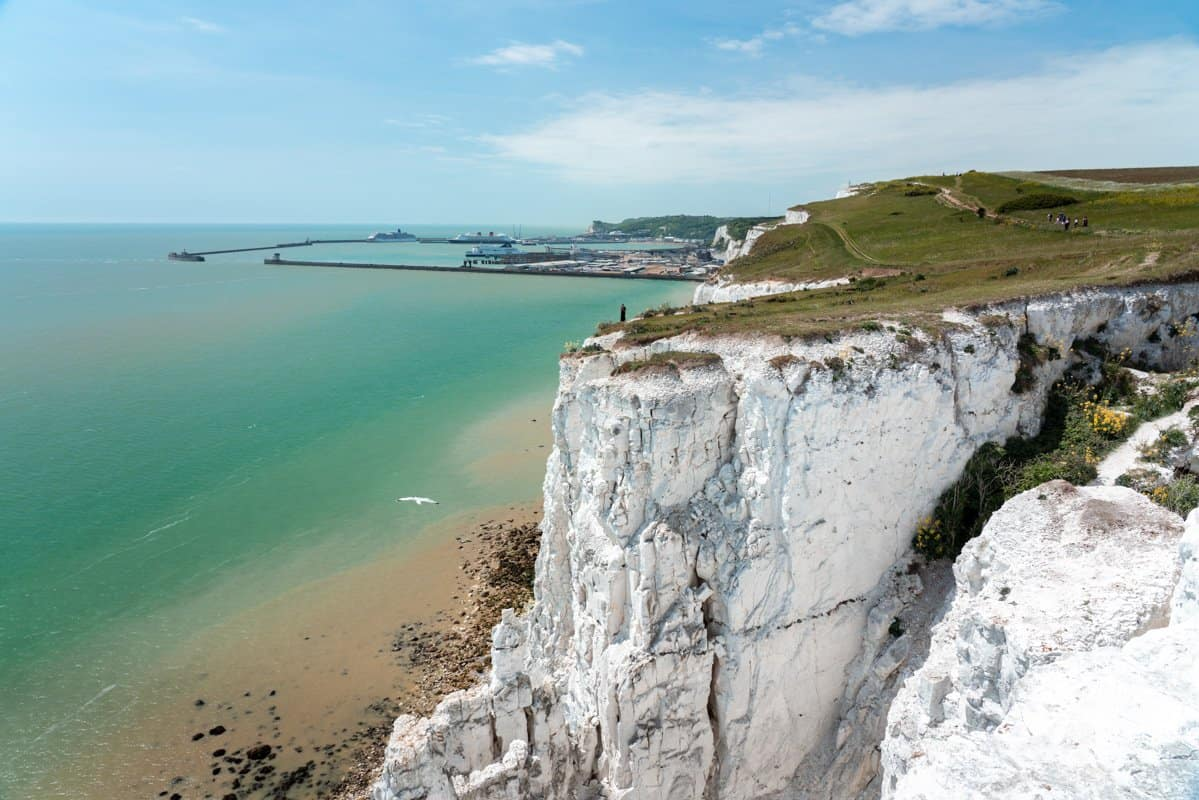 Looking back towards Dover Port from atop the White Cliffs with the exposed chalk face in the foreground and bright blue ocean.