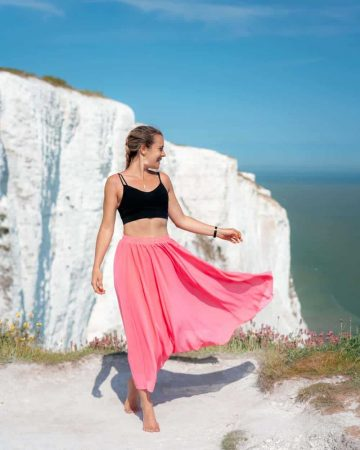 A girl in a pink skirt at a scenic lookout at the White Cliffs of Dover
