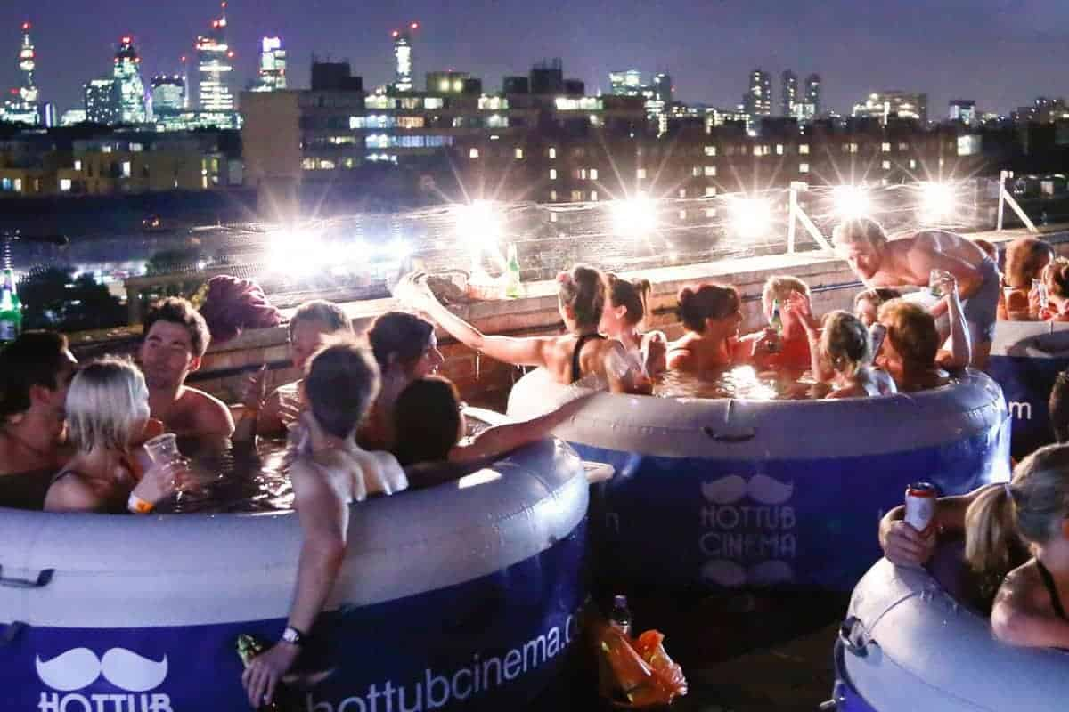 Crowded hot tubs on a roof tub in London at hot tub cinema; one of the best non touristy things to do in London