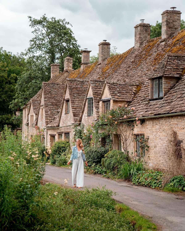 A girl walking along Arlington Row in the beautiful English village Bibury.