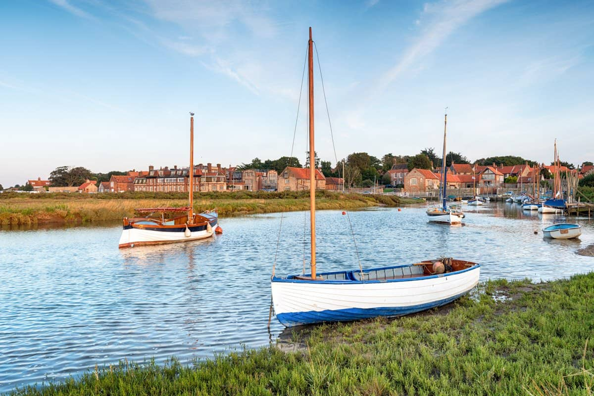Small sailboats in front of the coastal village of Blakeney, Norfolk, England