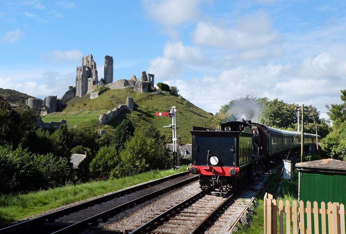 A steam train in front of the castle in Corfe Castle village, Dorset.
