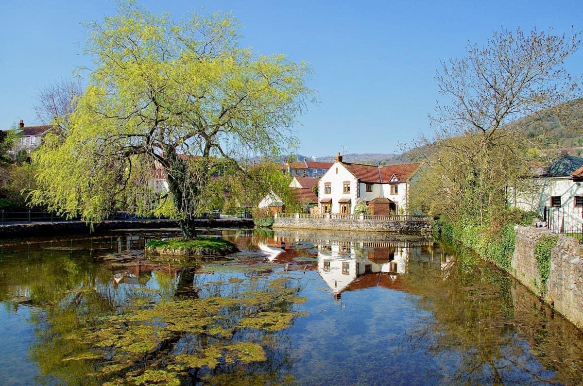 Pretty village of Cheddar, Somerset reflecting in still water.