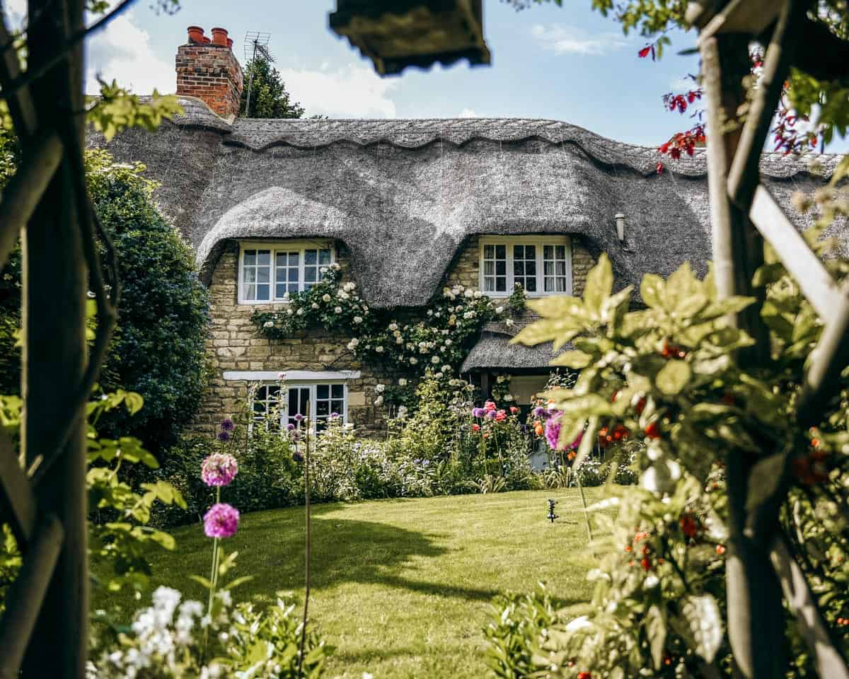 A cute thatched cottage with colourful flowers in the garden in the English village of Exton.