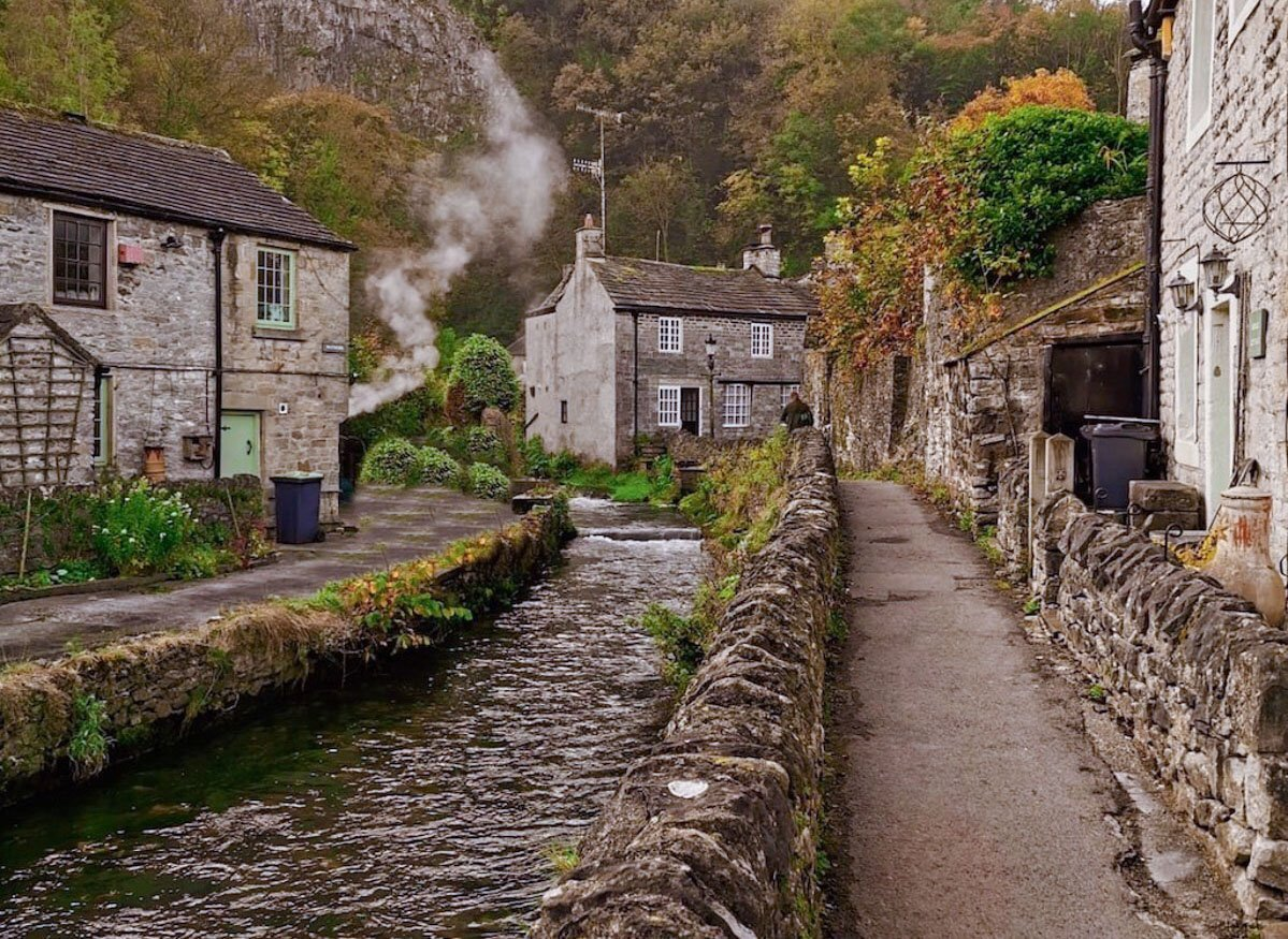 The picturesque English village of Castleton with a small stream running through it.