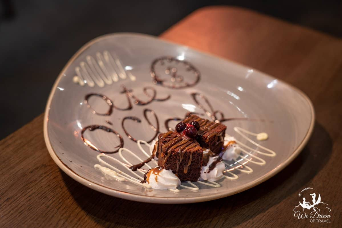 A plate of brownies with chocolate decoration.