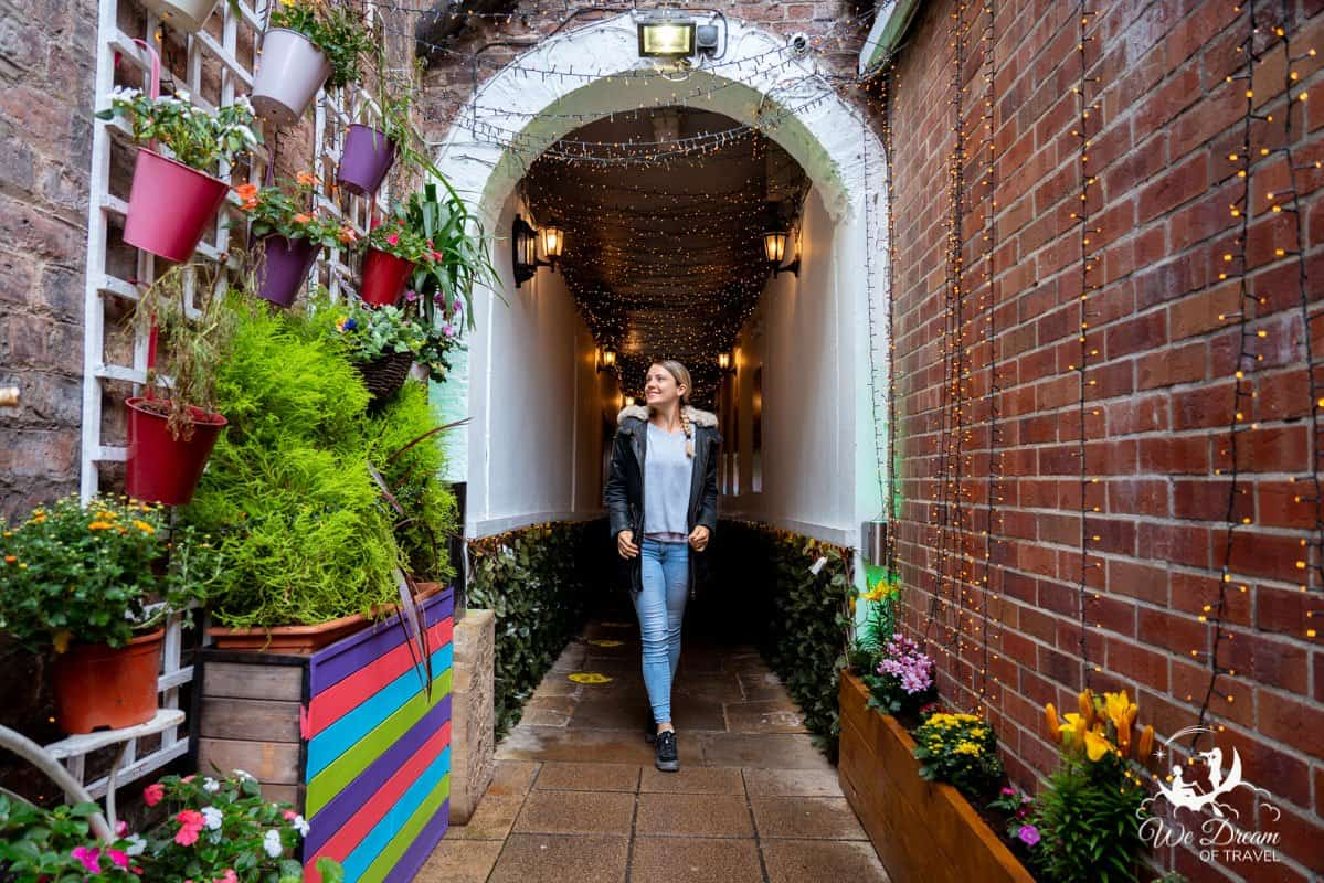 A girl standing in the fairy lit tunnel entrance way to Ate O'clock