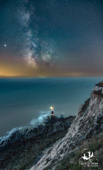 Night photography at Beachy Head Lighthouse shining against the Atlantic under a Milky Way sky.