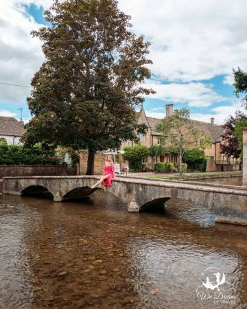 A girl sat on a bridge in Bourton on the Water Cotswolds village