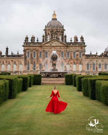 A girl in a red dress in front of Castle Howard - a great day trip from York