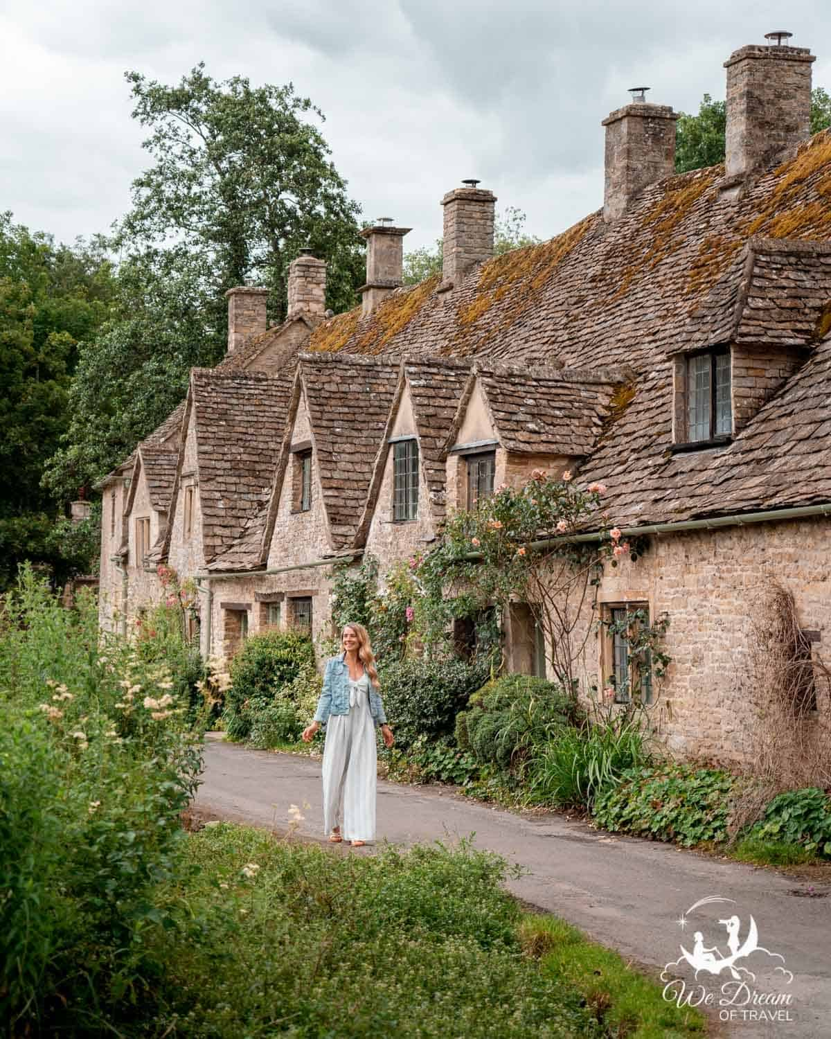 A girl walking along Arlington Row in the picturesque Cotswolds villages Bibury