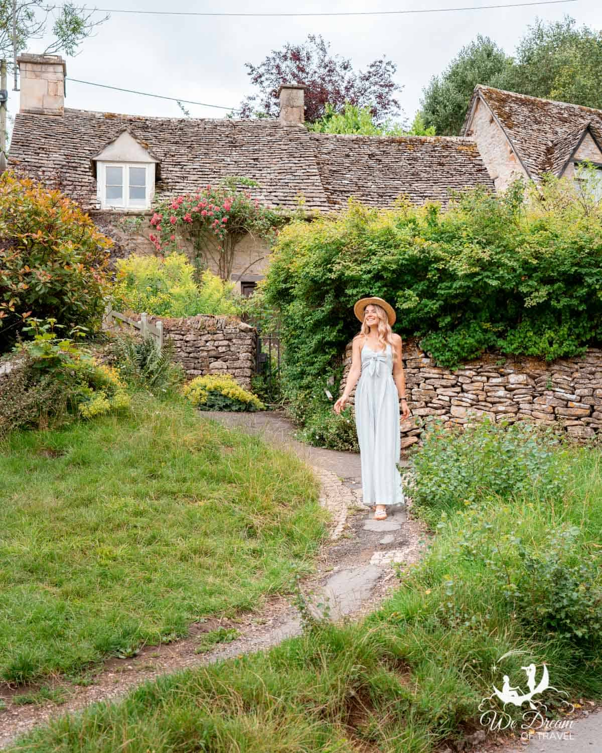 A girl in front of a stone cottage in the beautiful Bibury village Cotswolds