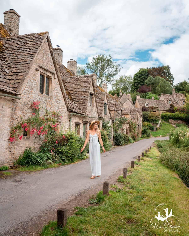 A girl walking down Arlington Row in the pretty Cotswold village of Bibury