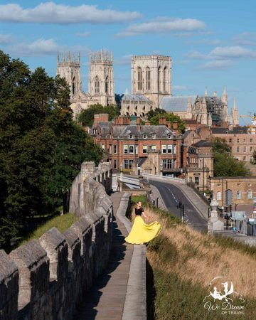 A girl in a skirt on the York city walls with York Minster and the city in the background.