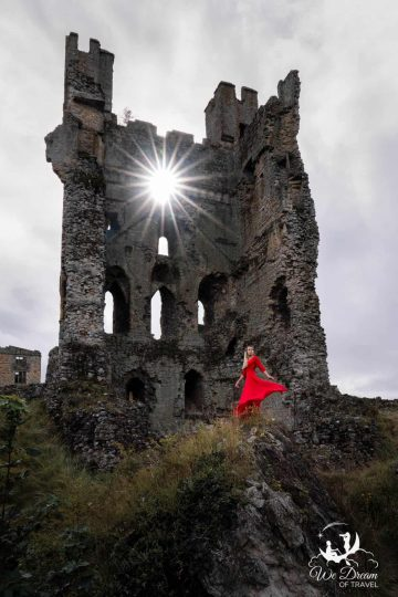 Sun star in the window of the medieval ruins of Helmsley Castle with a girl in a red dress on the rocks in front.