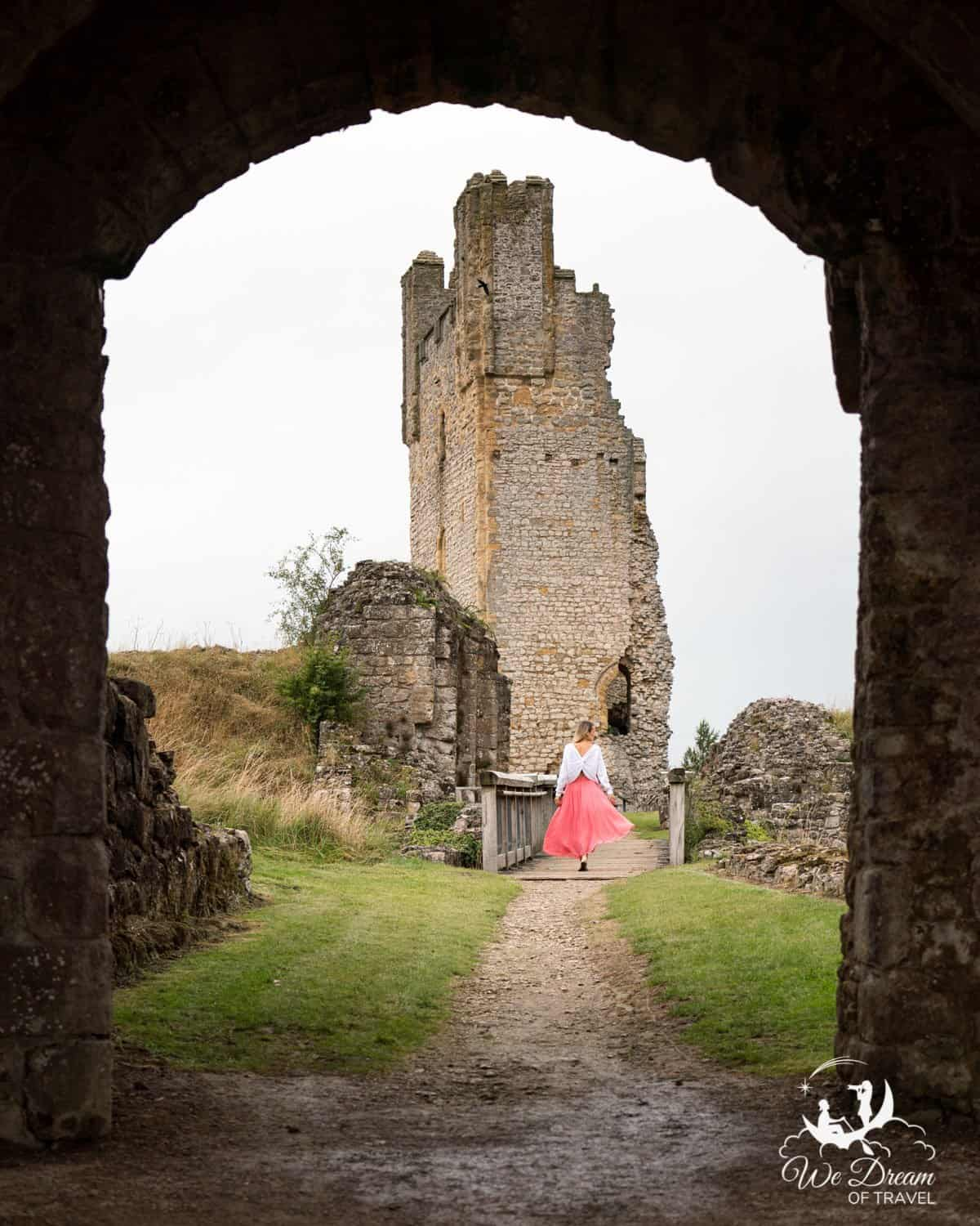 A girl framed by an archway in front of the tower of Helmsley Castle York