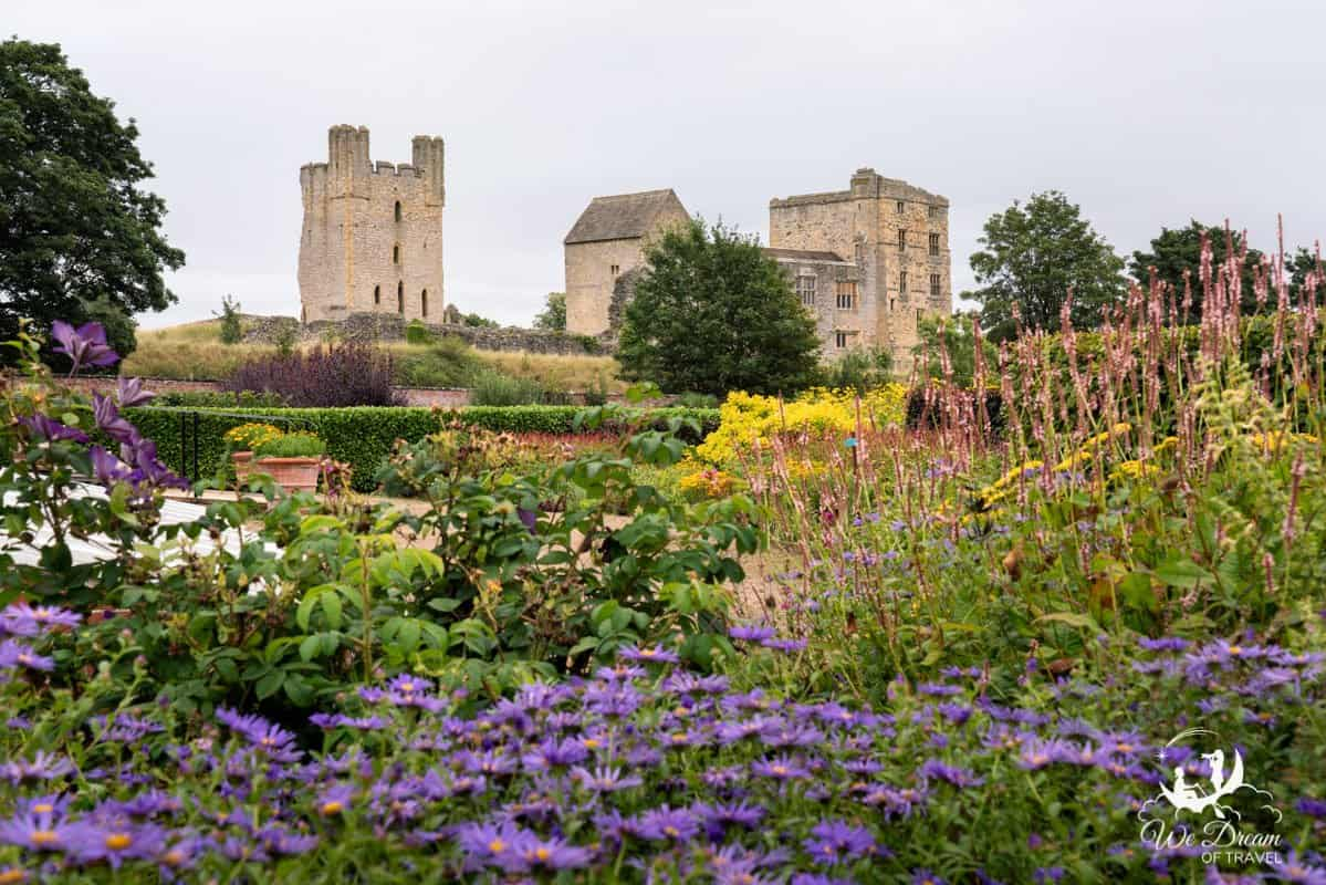An array of vibrantly coloured flowers at Helmsley Walled Gardens with the ruins of Helmsley Castle behind.