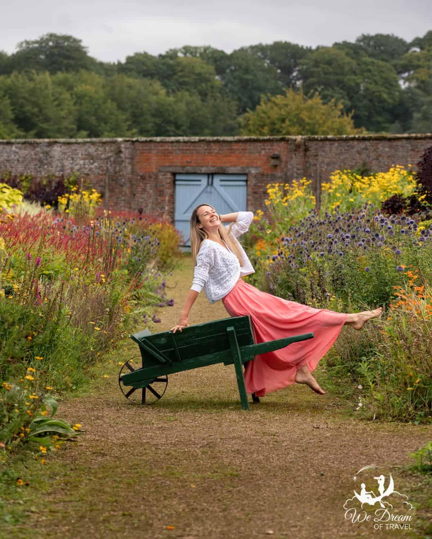 A girl sat on a wheelbarrow at Helmsley Walled Gardens.