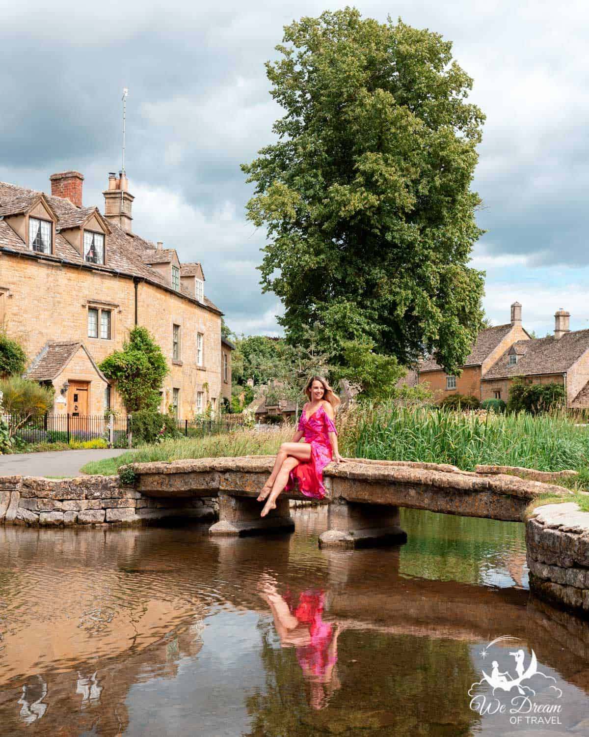 A girl sat on a footbridge in Lower Slaughter in the Cotswolds