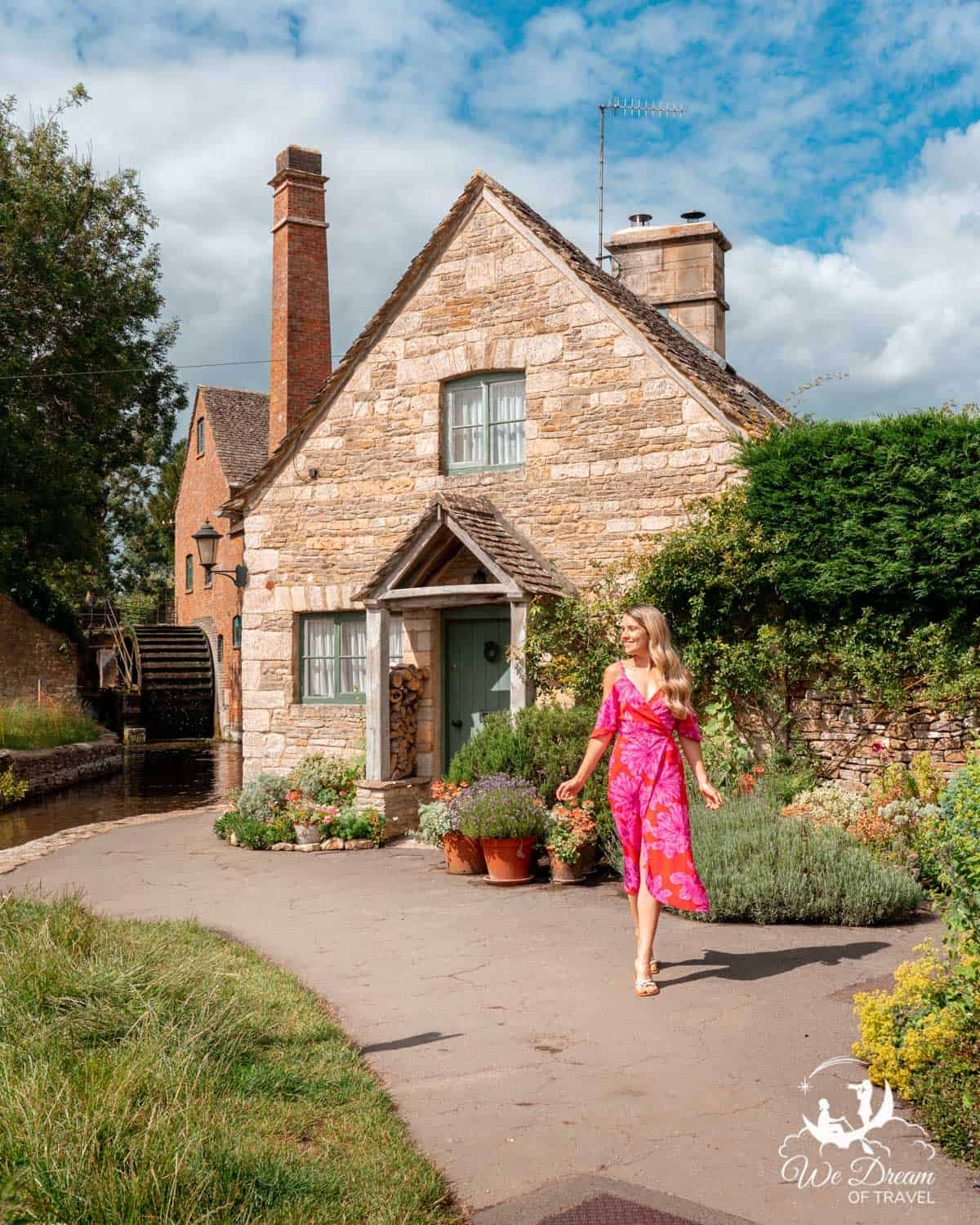 A girl in front of a cottage and mill in Lower Slaughter village in the Cotswolds