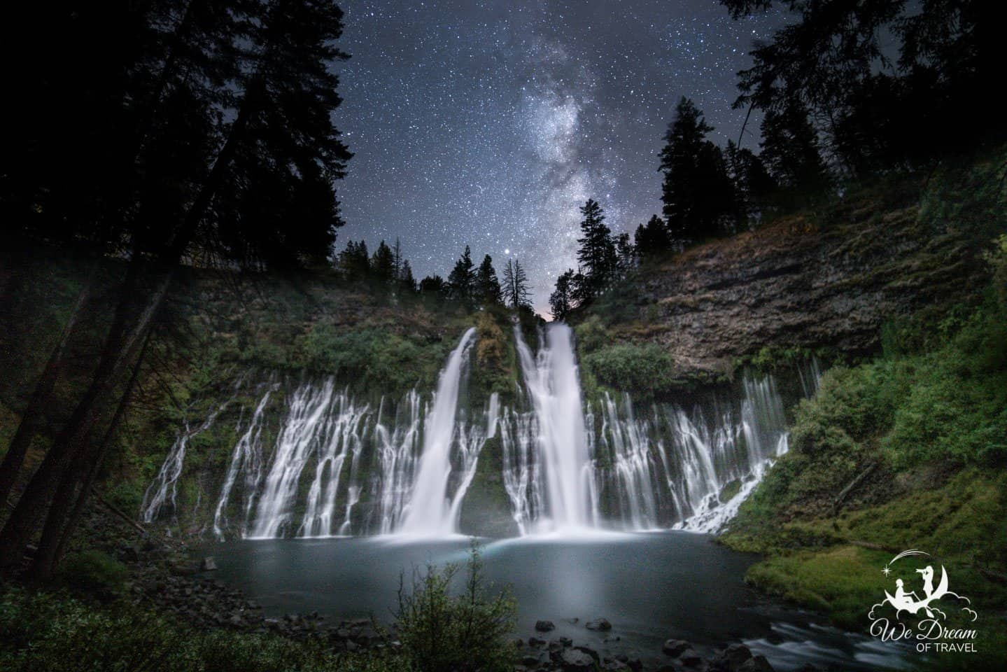 Long exposure waterfall photography at night with the milky way over the waterfall.