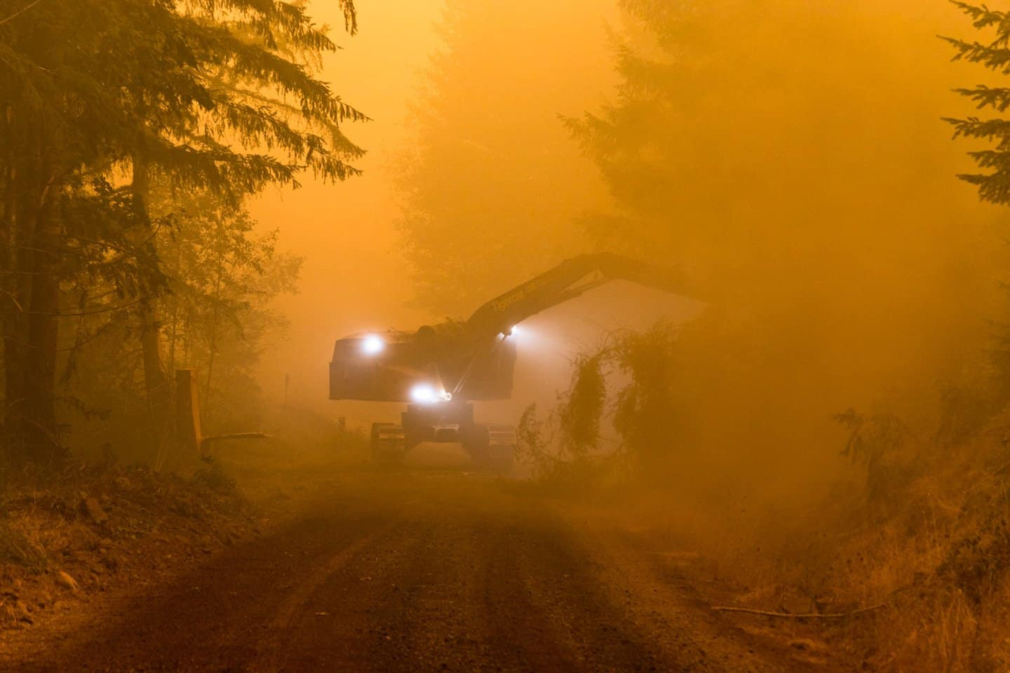 Clean up crews clear emergency evacuation roads following wildfires in the Pacific Northwest.