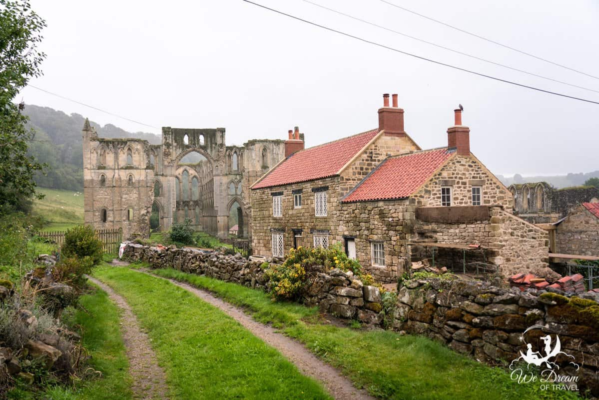 Rievaulx Abbey and brick houses seen from the roadside.